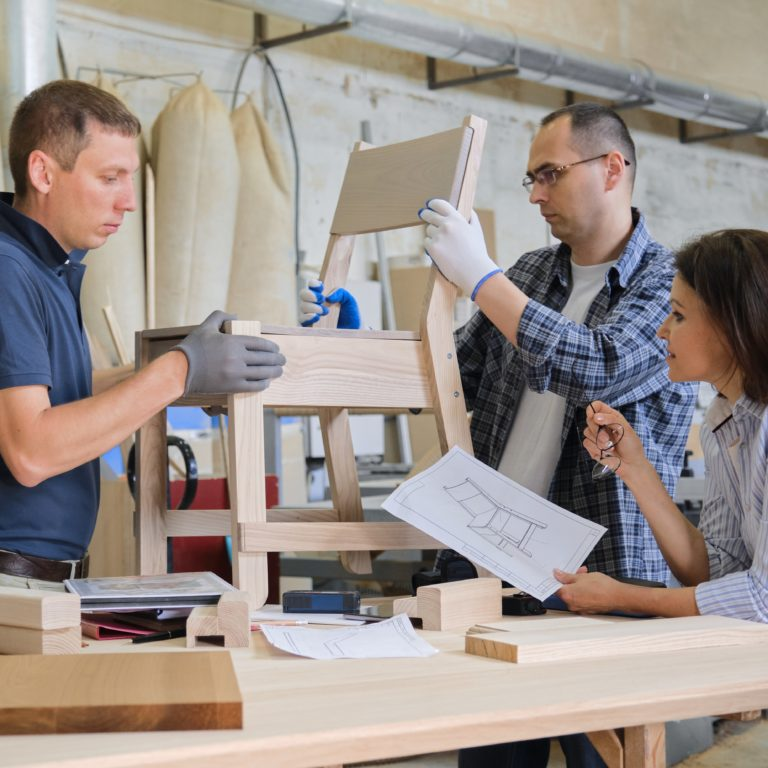 Group of working designers discussing production of new model of wooden modern chair, background carpentry workshop
